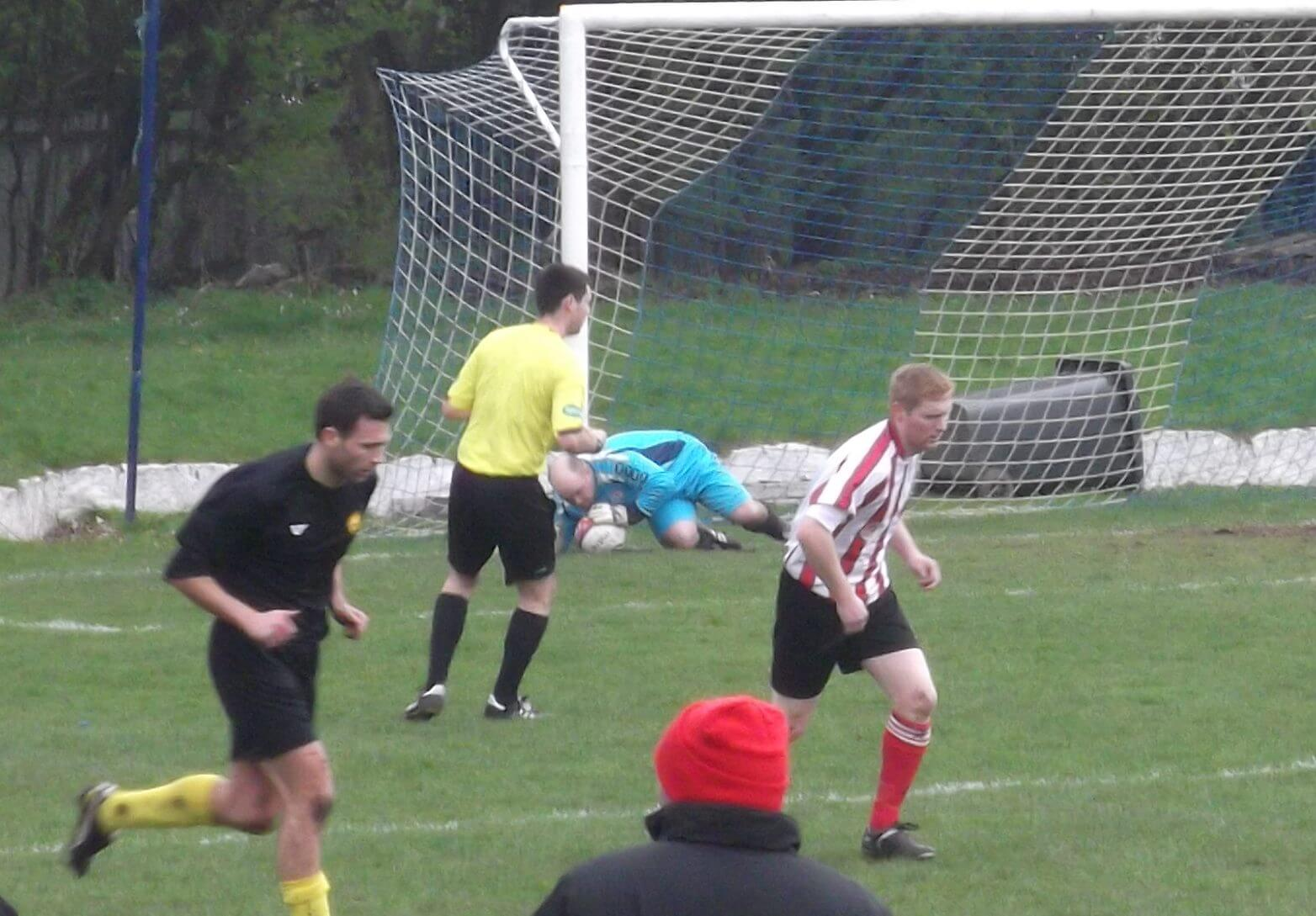 Jags keeper Lee Moss dives to smother goal attempt from Bellshill