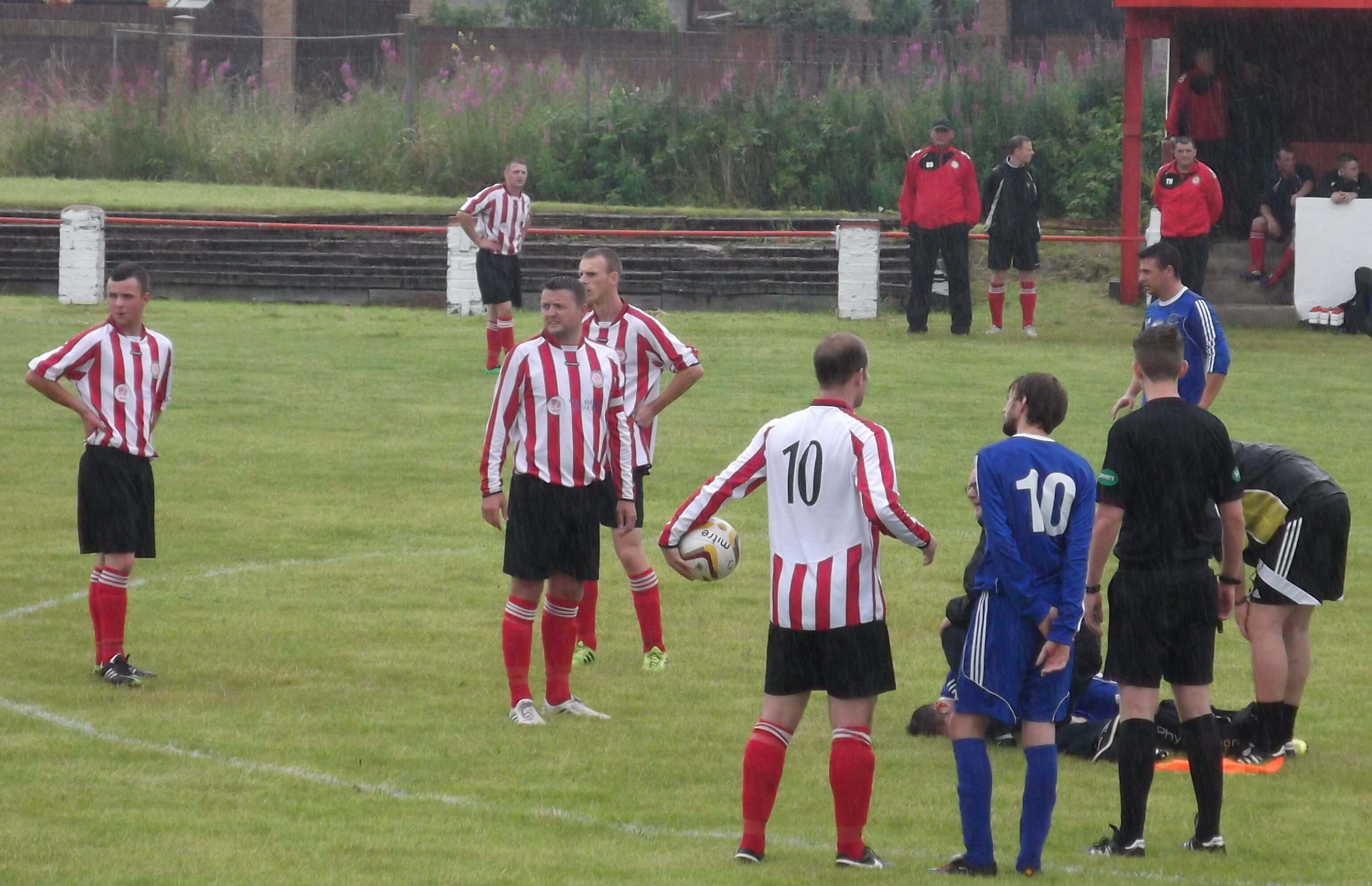 Players from both sides look on anxiously at injured Abbey Vale player